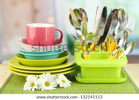 Plates, forks, knives, spoons and other kitchen utensil on bamboo mat, on bright background