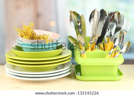 Plates, forks, knives, spoons and other kitchen utensil on bright background
