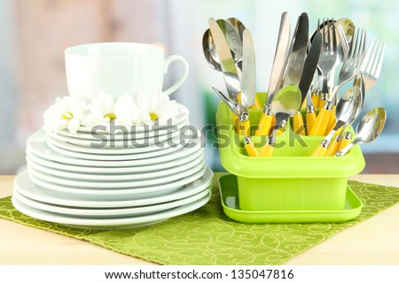 Plates, forks, knives, spoons and other kitchen utensil on color napkin, on bright background
