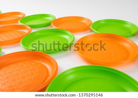 Plates in rows. Cheap plastic dishes for everyday use lying together and showing affection on environment