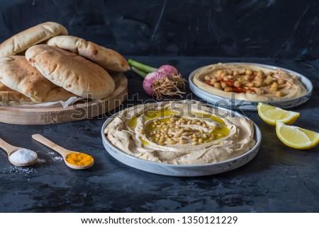 plates of hummus with pita bread on black background  ストックフォト ©