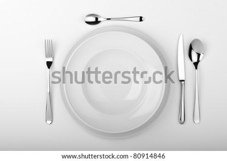 Plates with a silver fork, spoon, dessert spoon and a knife isolated on white studio background - stock photo