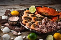 Plates with assorted seafood. Cooked crab, baby octopuses and tiger shrimps served with ice cubes, lime and seashells on rustic wooden background. Seafood concept. Delicious for gourmet.