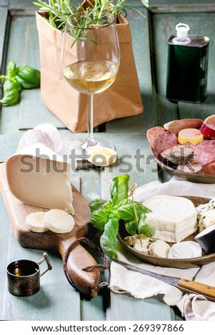 Plates with cheese and sausage variations with fresh basil and glass of white wine over turquoise wooden table. Overhead view.