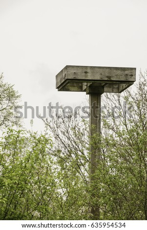 Platform for an osprey nest above a lake and woods in springtime, northern Illinois, USA, for themes of raptors and wildlife, conservation, elevation