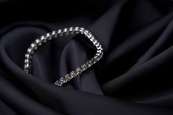 Platinum bracelet with diamonds on black silk background. White gold bracelet with gemstones, close-up. Elegant woman jewelry
