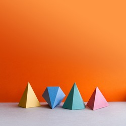 Platonic solid geometric figures. Three-dimensional pyramid rectangular triangle objects on orange gray background. Yellow blue red green colored tetrahedron abstract shapes objects. copy space