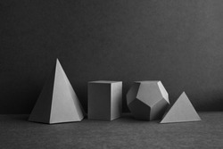 Platonic solids figures geometry. Abstract geometrical figures still life composition. Three-dimensional prism pyramid cube objects on black gray background
