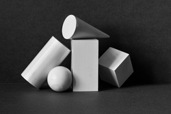 Platonic solids figures geometry. Abstract geometrical objects still life composition. Three-dimensional rectangular prism, cylinder pyramid cube, sphere on black gray background.