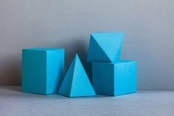 Platonic solids figures geometry. Abstract turquoise color geometrical figures still life composition. Three-dimensional prism pyramid rectangular cube objects on gray background