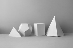Platonic solids figures geometry. Abstract white color geometrical figures still life composition. Three-dimensional prism pyramid rectangular cube objects on gray background
