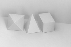 Platonic solids figures geometry. Abstract white color geometrical objects still life composition. Three-dimensional prism pyramid rectangular cube on gray background
