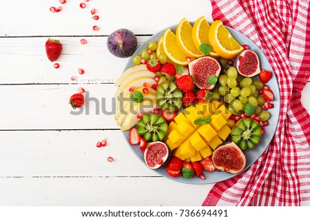 Platter fruits and berries. Mango, kiwi, fig, strawberry, grapes, pear and orange. Vegan cuisine. Dietary menu. Flat lay. Top view