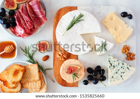 Platter of assorted cheeses and cured meats. Top view table scene on a bright background. #1535825660