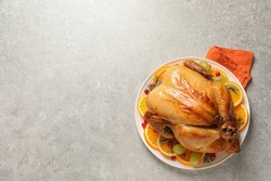 Platter of cooked turkey with garnish on grey background, top view. Space for text