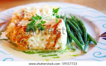 Platter of perfectly grilled sturgeon fish with sauce of white wine and side of green beans