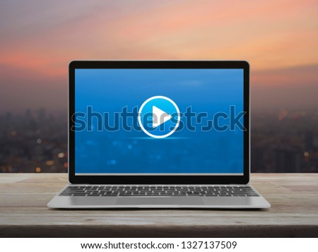 Play button with modern laptop computer on wooden table over blur of cityscape on warm light sundown, Business music online concept #1327137509