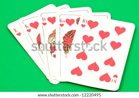 Play cards shows a winning hand, royal flush on green textured background