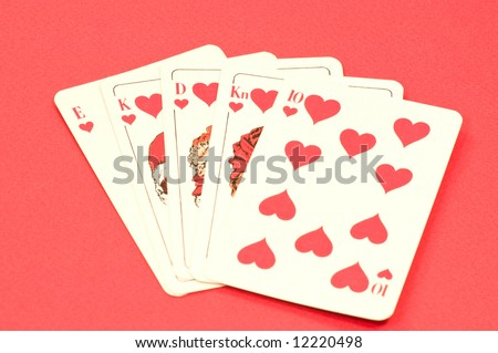 Play cards shows a winning hand, royal flush on red textured background