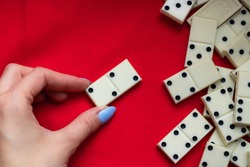 Play dominoes. A female hand lays domino bones on a red cloth next to a bunch of dominoes and a lot of space for text