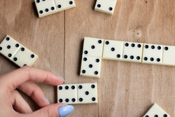 Play dominoes. Female hand puts domino bone on a brown table.