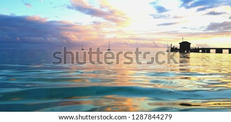 Play of colours on the water surface during a sunset with silhouettes of a jetty, a boathouse and boats in the distance #1287844279
