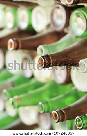 Play of light, reflection and transparency on a wall of empty beer bottles
