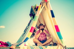 Play tent. Summer camp. Camping in improvised wooden house in nature. Bearded man in hovel on sky background. Hovel decorated party