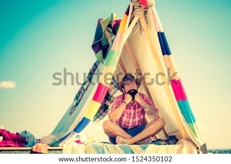 Play tent. Summer camp. Camping in improvised wooden house in nature. Bearded man in hovel on sky background. Hovel decorated party #1524350102