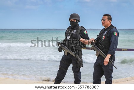 PLAYA DEL CARMEN, MEXICO - JANUARY 2012: Two military police officers patrolling  the beach in Playa Del Carmen during International Music Festival. #557786389