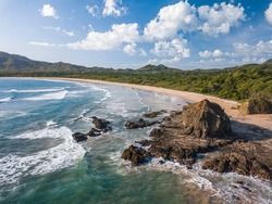 Playa Grande, Guanacaste, Costa Rica - Aerial Drone shot of large Tropical Beach with big Rocks - A Surfers Paradise