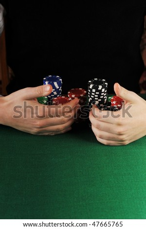 player is grabbing gambling chips that he won on a card game.