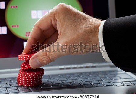 Player placing chips on a laptop which shows an online casino - online gambling concept; focus on the chips