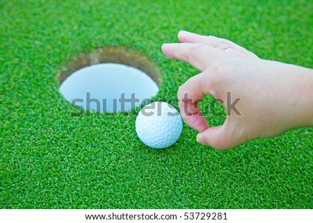 Player putting golf ball in the hole