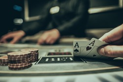 player shows one pair of aces in poker against the background of playing chips on a green table in a casino close-up