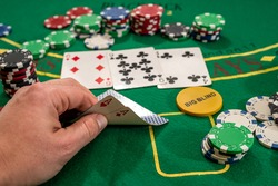 player shows two play card aces on a green table in a casino wirh chips. gambling