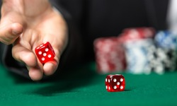 Player throws dices on the poker table. Symbol of addiction to the poker