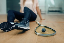 Player with squash racket and ball sits on floor