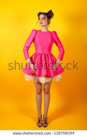 Playful and stylish brunette girl in the image of the doll on a yellow background. Woman looks like a doll. An unusual image for a party. Stock photo ©