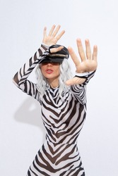 Playful androgenic  model in freak stylish zebra print clothes and leather trendy black cap posing in a white studio. Clubbing party style