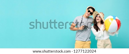 Playful Asian couple in summer casual clothes with beach accessories studio shot isolated on light blue banner background with copy space #1277122024