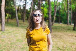 Playful beautiful young woman showing tongue while sitting in the sun in the park - Happy cute girl wearing sunglasses acting silly and having fun in nature - Casually dressed female relaxing outside
