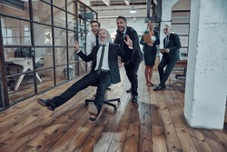 Playful businessmen pushing their boss on the office chair while running in the hallway