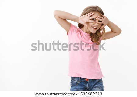Playful charismatic blond girl, peeking through fingers, cover eyes with palms smiling and laughing joyfully, playing hide-n-seek fool around, curiously observe what happening, b-day kid have fun Foto stock ©