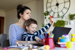 Playful child annoying his mother while she tries to tele work. Telecommuting issues and family conciliation concept.