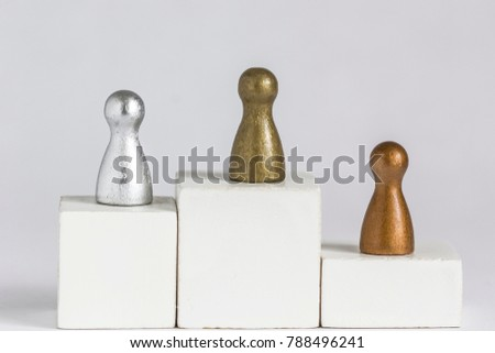 Playful Concepts: Gold, Silver and Bronze gamefigurine on a winner podium #788496241