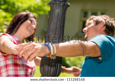 Playful couple having fun in the park happy smiling love