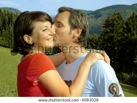 Playful couple is kissing in the nature. Unique keyword for this collection: lovely77