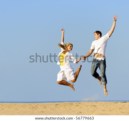 Playful couple jumping and smiling on the beach