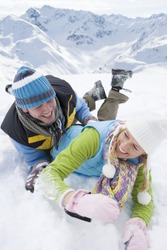 Playful couple laying in snow with mountain in background